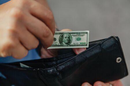 Toy money. A hand is hiding a miniature dollar bill in a black purse