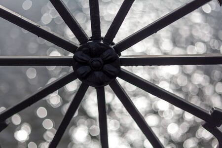 Round design with radial rays on a blurry shiny background.