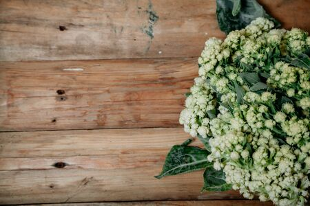 Autumn still life. Cauliflower head on the old planed wooden boards closeup
