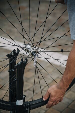 Hand removes a bicycle wheel from the support fork of a modern bicycle close up