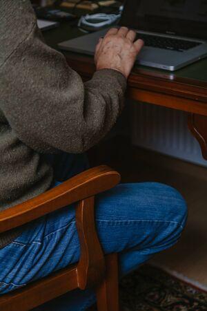 l'uomo si siede davanti a un tavolo su cui c'è un laptop.