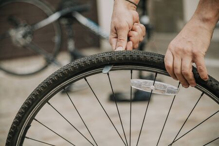 Hands remove the tire from the rim of the bicycle wheel with the help of a special flat tool close up Imagens
