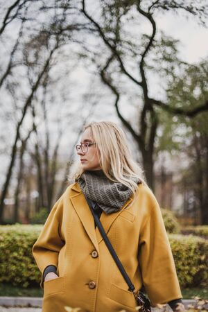 beautiful blonde in glasses and walking in an autumn park on her bright yellow fashion coat