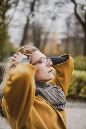 Portrait of a young woman in glasses with long blond hair in a yellow coat in an autumn park 免版税图像