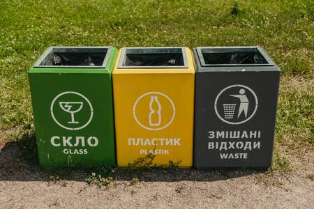 Separate garbage collection. Three containers of different colors for collecting different types of garbage are on the ground in front of a grass lawn Stock fotó