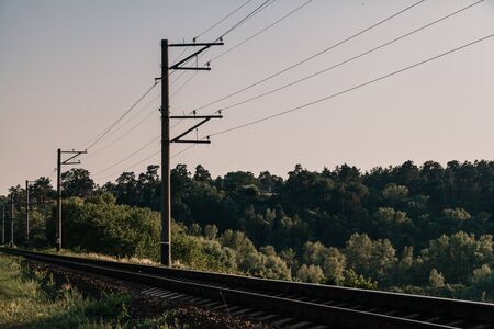 Single track railway. Power transmission towers are installed along it against a cloudy sky.