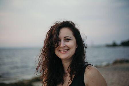 Retrato de una chica guapa con pelo largo rojo en el fondo de una orilla del mar borrosa. Foto de archivo