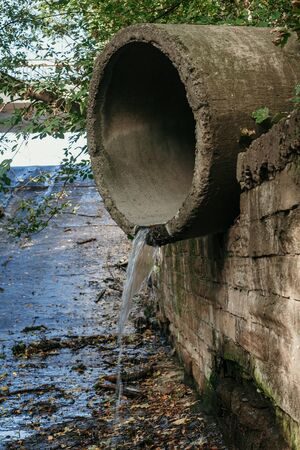 Concrete pipe storm drainage system close-up. A stream of water flows out of the pipe