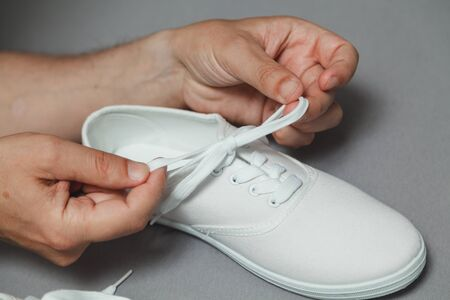 Tanned hands tie shoelace on white sneaker against gray background close up Stok Fotoğraf