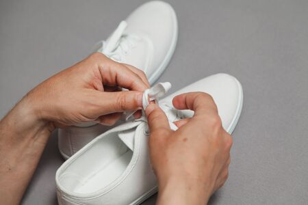 Tanned hands tie shoelace on white sneaker against gray background close up Imagens