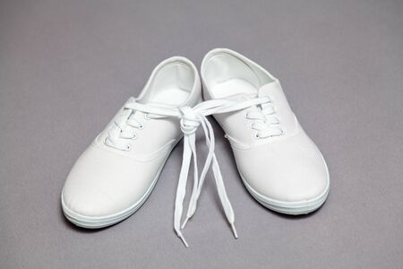 Two new white sneakers with laces stand on a gray isolated background. Laces tied in a common knot Stok Fotoğraf