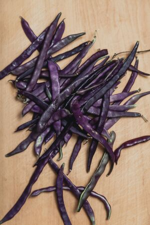 Pods of purple bean lie on a wooden board