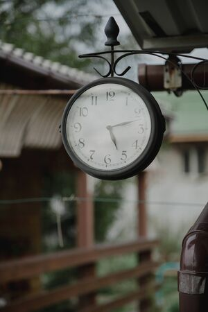 Beautiful street clock round shape mounted on a metal bar in the yard