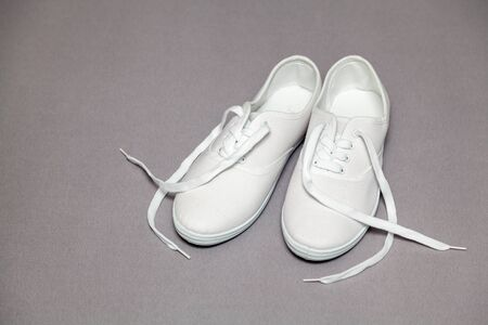 Two new white sneakers with laces stand on a gray isolated background Imagens