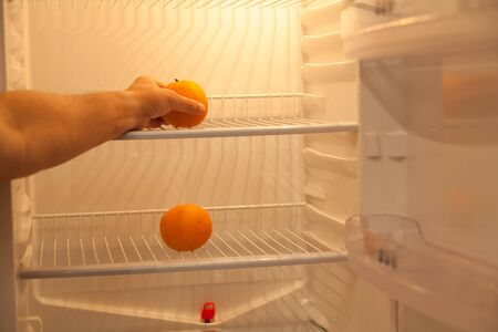 Empty fridge. Two oranges lie on different shelves one above the other. The hand takes the orange from the top shelf.