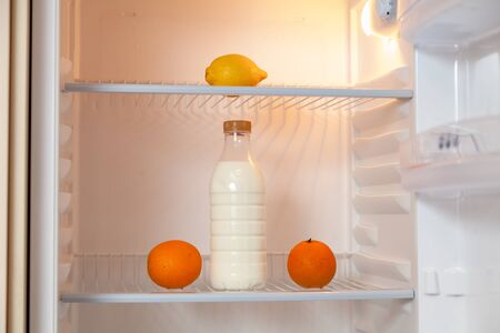 plastic bottle of milk is on the shelf of an empty fridge. Nearby are two oranges. Lemon is on the top shelf