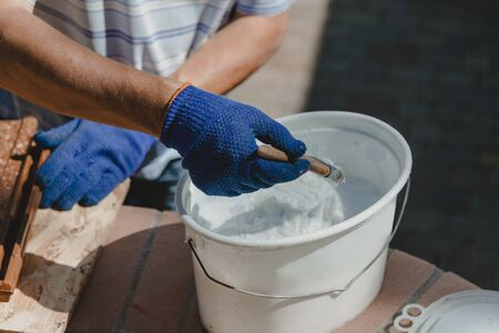 Painting works. A hand in a working glove dials a special white mastic from a plastic container onto a brush. Close-up Imagens