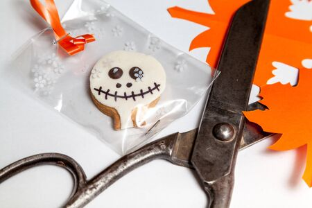 Cheerful Halloween. Round Halloween cookies in the package on a white background. Nearby are old scissors and paper leaves