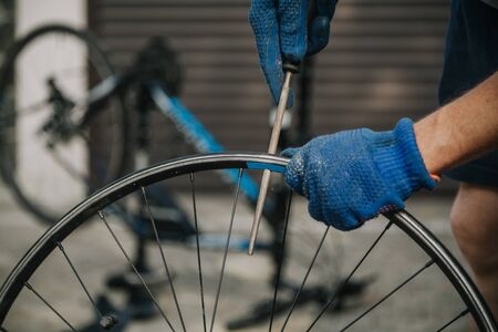 Repair bicycle wheel. The cyclist cleans a hole in the rim of the wheel with a round file Banco de Imagens