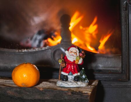 Before modern fireplace standing on logs figure of Santa Claus and Mandarin. Nearby stands a Christmas tree with toys