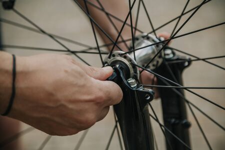 hand opens the lock and lever-type bushings on the fork modern cycling wheel Banco de Imagens