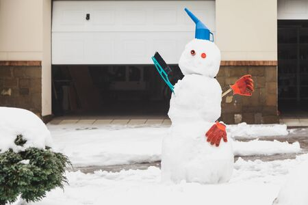 Snowman motorist stands in front of the garage. For decoration use a watering can, a brush and working gloves Imagens