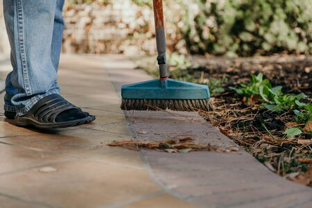 worker collects yellow pine needles on a brick walkway with a wide brush on a long handle close up Imagens