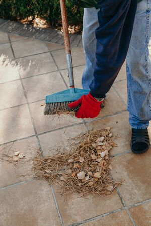 Autumn cleaning. A worker in a red working glove picks up pine needles stuck in a wide brush. And piles on a square paving slab
