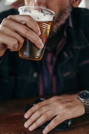 hand is holding a plastic glass of beer from which a man in a denim jacket is drinking beer in close-up