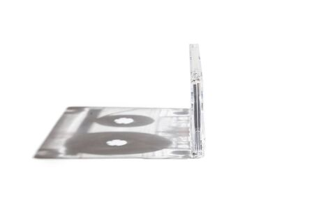 Original perspective. The audio cassette with a transparent case stands perpendicularly on a white background. Left interesting shadow