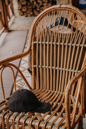 Autumn fashion. A brown hat lies on a wicker chair on the autumn porch. Knitted jacket weighs on the back. Stockfoto