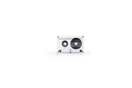 Audio cassette for tape recorder with a transparent plastic case on a white background close-up