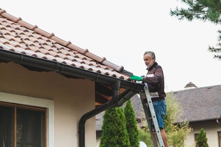 adult man stands on a metal staircase and repairs a tiled roof against a cloudy sky.
