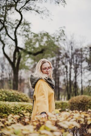 beautiful blonde with glasses and walks between shorn bushes in an autumn park on her bright yellow fashion coat