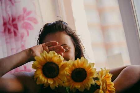 Romantic Awakening. Beautiful girl in the morning received a bouquet of yellow flowers of sunflower 写真素材