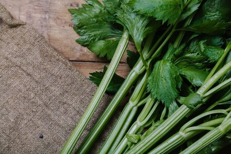 bunch of large green odorous celery lie on a canvas closeup