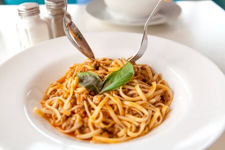 Hands holding a spoon and fork over appetizing spaghetti on a round plate decorated with green leaves close up. Banque d'images