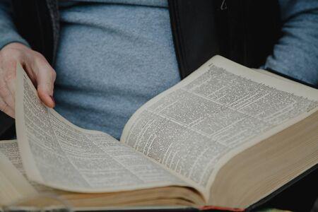 Nous lisons le dictionnaire. Un livre épais ouvert de grand format se trouve devant un homme en pull bleu