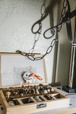 Halloween in the workshop. Cookies for Halloween is in the box with a set of tips for engraving. Hanging vintage scissors and a chain Imagens - 130676194