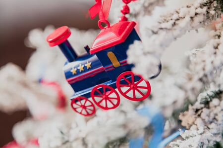 original Christmas tree toy is a blue steam locomotive with red wheels weighing on a Christmas tree. Around the red garland