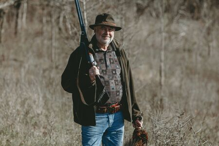 Portrait of a lucky hunter. Adult hunter in a hat with a double-barreled gun on his shoulder holds a trophy