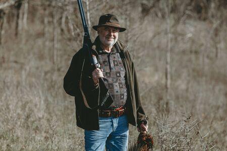 Portret van een gelukkige jager. Volwassen jager in een hoed met een dubbelloops pistool op zijn schouder houdt een trofee vast