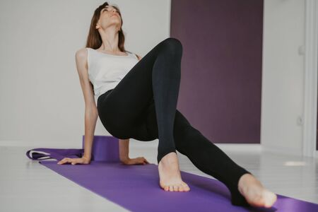 Cute graceful girl with long hair in tights engaged in yoga on a lilac rug