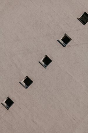 Geometric correct background. A row of square windows located on a gray wall.