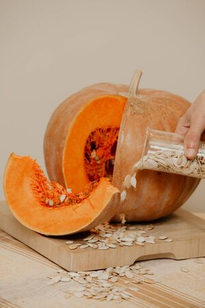 Beautiful round pumpkin lies on a square wooden board with a hand spills seeds from a glass cup