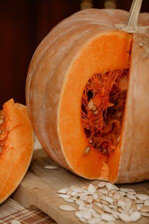 Orange autumn still life. A slice of ripe orange pumpkin lies in front of a large round pumpkin. Near white seeds