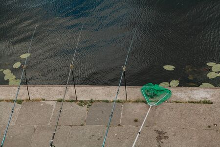Fishing in the city. Three long fishing rods are installed on the concrete embankment on the shore of the reservoir. There is a green net next Imagens - 130708170