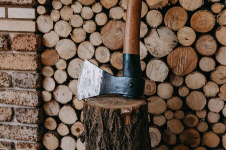 Ax with sharpened blade stands on a stump in front of stacked chopped firewood of circular cross section close up