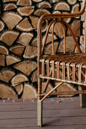 beautiful wicker rattan chair stands in the background of a niche with chopped wood