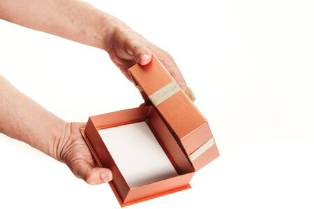 We choose packaging for a gift. Hands opened an empty box with a bow on the lid and a white bottom close-up.